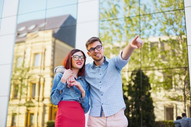 Feliz casal jovem dançando na rua da cidade e rindo no dia ensolarado