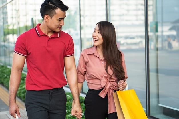 Feliz casal jovem de compradores andando na rua comercial em direção e segurando sacolas coloridas