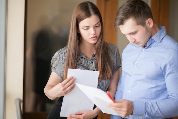 Feliz casal jovem de profissionais estão de pé em um escritório de vidro contemporâneo