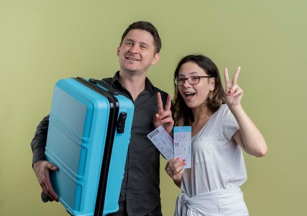 Feliz casal jovem de turistas, homem e mulher segurando mala e passagens aéreas, sorrindo, mostrando o sinal-v em pé sobre a parede de luz