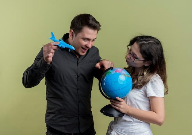 Feliz casal jovem de turistas, homem e mulher segurando o avião de ar globo e brinquedo juntos, se divertindo com a luz