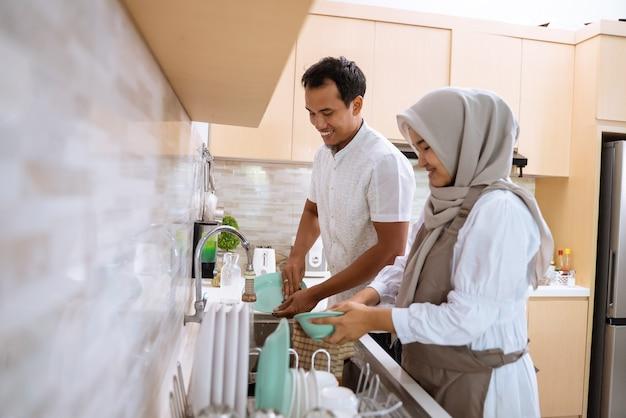 Feliz casal jovem muçulmano lava a louça depois de jantar iftar juntos na pia da cozinha