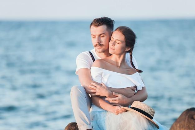 Feliz casal jovem romântico relaxante na praia e assistir o pôr do sol