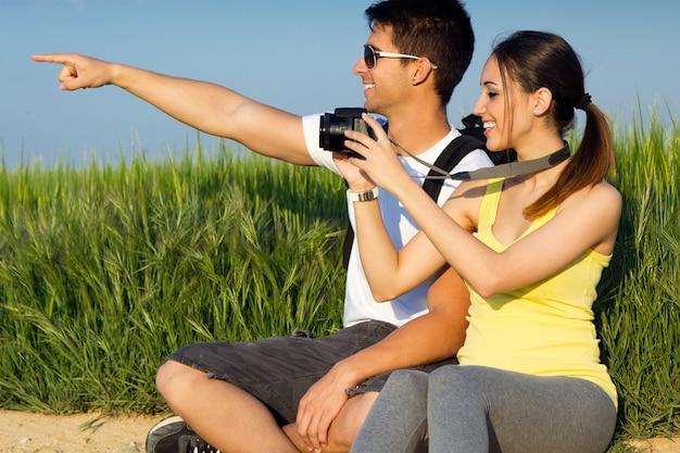 Feliz casal jovem tirando fotos no campo