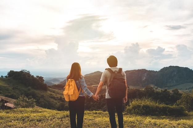 Feliz casal jovem viajante relaxando e olhando o belo pôr do sol no topo da montanha