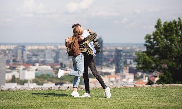 Feliz casal jovem viajantes na cidade de férias, se abraçando. paisagem urbana em segundo plano.