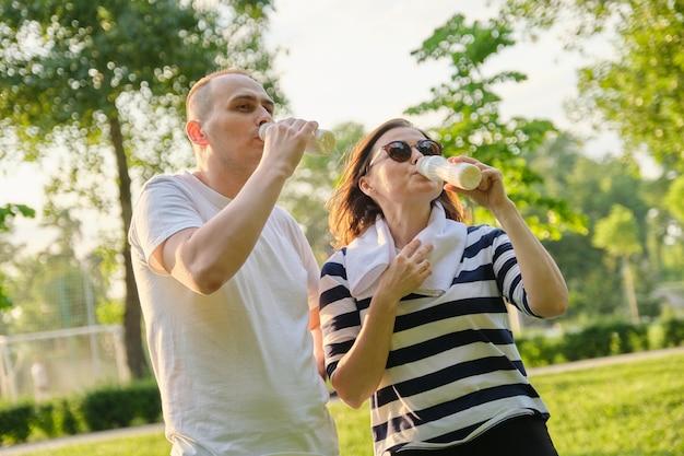 Feliz casal maduro no parque, descansando, bebendo iogurte, laticínios após exercícios esportivos