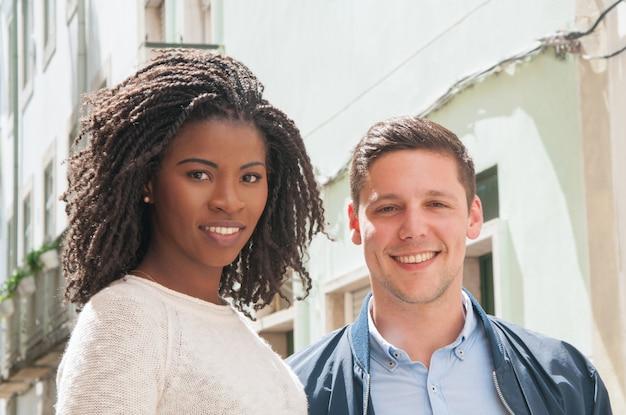 Feliz casal multicultural posando ao ar livre