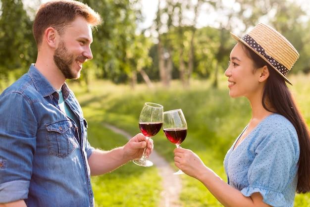 Feliz casal multiétnico tinindo copos de vinho no parque