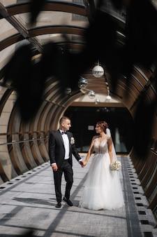 Feliz casal recém casado andando linda janela redonda no dia do casamento.