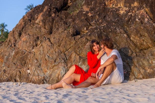 Feliz casal romântico na praia tropical ao pôr do sol.