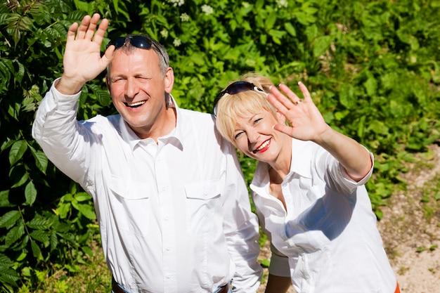 Feliz casal sênior ao ar livre, agitando as mãos