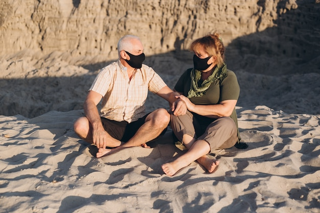 Feliz casal sênior apaixonado usando máscara médica para proteger de coronavírus, praia, quarentena de coronavírus