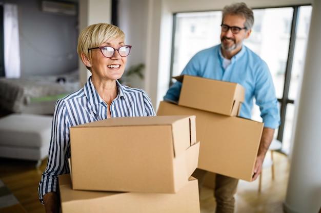 Feliz casal sênior aposentado apaixonado, mudando-se para uma nova casa, apartamento.