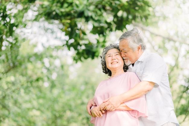 Feliz casal sênior asiáticos abraçados