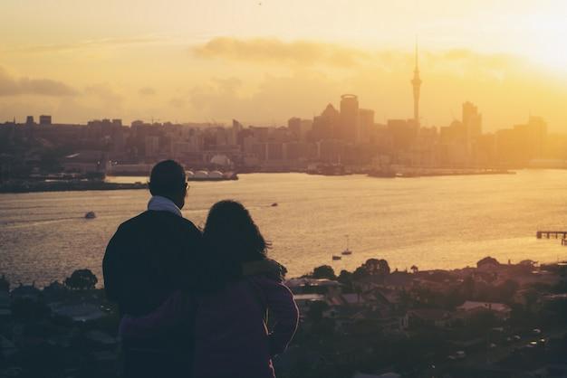 Feliz casal sênior assistindo o pôr do sol em auckland