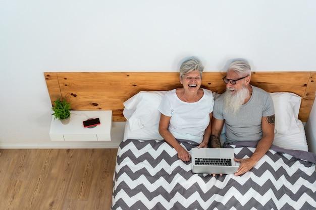 Feliz casal sênior assistindo vídeos, sentada na cama, rindo juntos