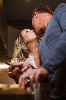 Feliz casal sênior beijando na cozinha