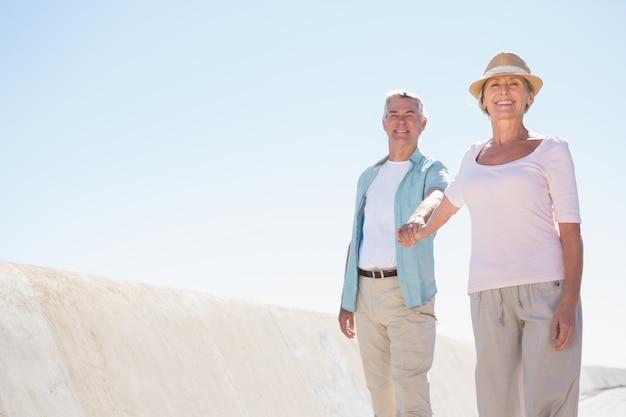 Feliz casal sênior caminhando no cais