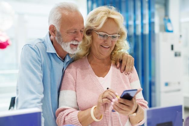 Feliz casal sênior comprando novo telefone inteligente na loja de tecnologia. mulher experimentando telefone inteligente enquanto o marido em pé atrás dela e a observando.