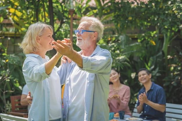 Feliz casal sênior dançando depois do café da manhã com a família em casa jardim