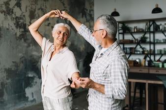 Feliz casal sênior dançando em casa