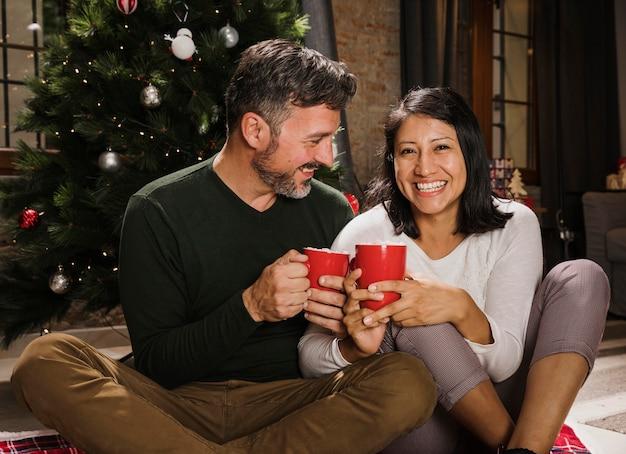 Feliz casal sênior de natal enoying bebidas quentes