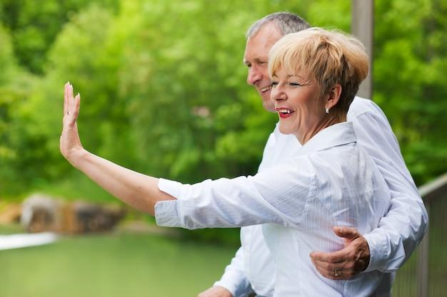 Feliz casal sênior na ponte acenando as mãos