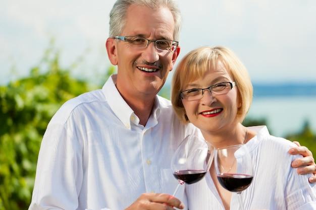 Feliz casal sênior posando com taças de vinho na frente de um lago