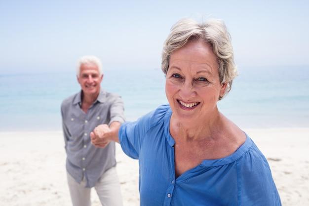 Feliz casal sênior segurando a mão na praia