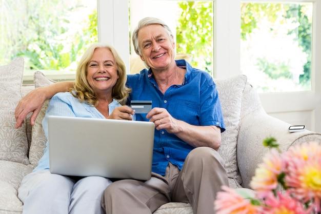 Feliz casal sênior segurando o cartão inteligente com o laptop enquanto está sentado em casa