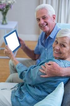 Feliz casal sênior segurando o tablet digital