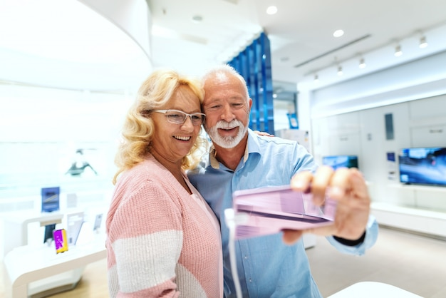 Feliz casal sênior tomando selfie com telefone inteligente que eles querem comprar. interior da loja de tecnologia.