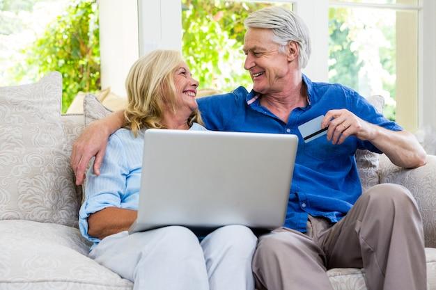 Feliz casal sênior usando o laptop em casa