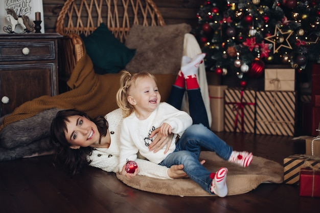 Feliz casual jovem mãe linda filha sorridente se divertindo no tiro completo do fundo da árvore de natal. linda família sentindo amor e emoções positivas curtindo a decoração de natal cercada por flocos de neve