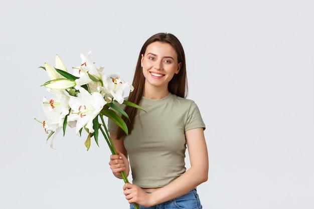 Feliz caucasiana jovem bonita receber entrega de buquê, sorrindo para a câmera como segurando flores. menina comprar lírios para sua casa, em pé fundo branco satisfeito