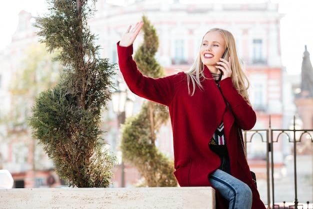 Feliz caucasiana jovem falando por telefone, acenando para os amigos.