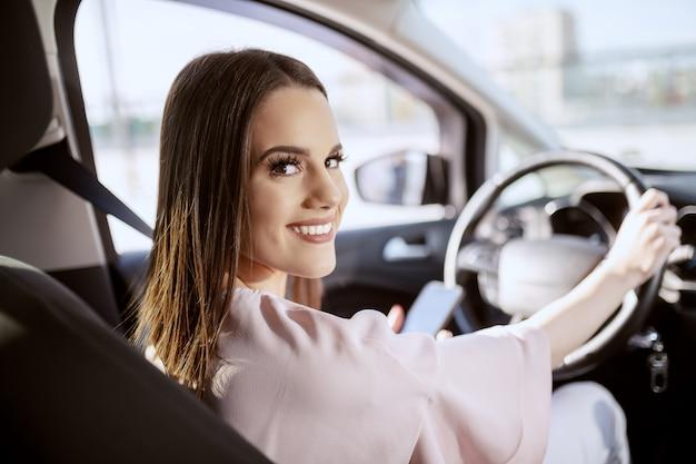Feliz caucasiana morena dirigindo seu carro e usando telefone inteligente enquanto olha para a câmera. foto tirada do banco traseiro.