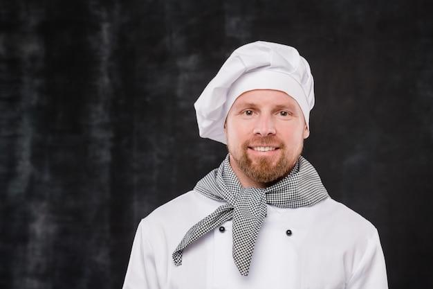 Feliz chef barbudo de uniforme branco olhando para a câmera com um sorriso em pé contra um fundo preto