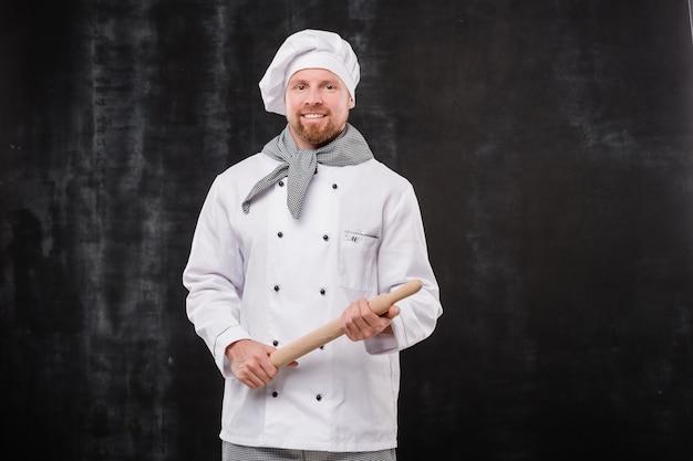 Feliz chef barbudo de uniforme branco segurando um rolo de madeira enquanto fica em frente à câmera contra um fundo preto