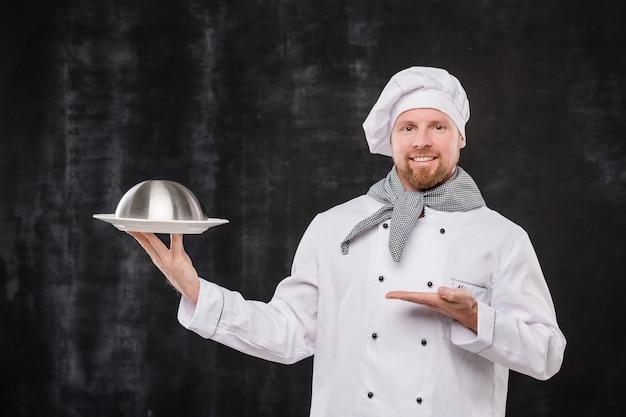 Feliz chef barbudo do restaurante com uniforme branco apontando para o cloche com refeição cozida em pé contra um fundo preto