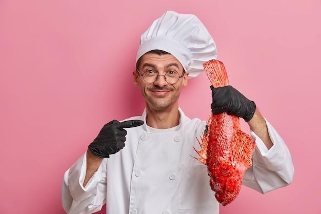 Feliz chef profissional masculino aponta para robalo vermelho grande, vai cozinhar uma refeição gourmet, vestido com uniforme branco e chapéu de padeiro