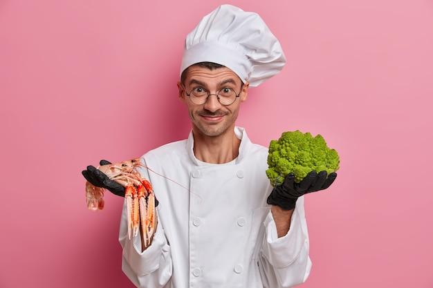 Feliz chef profissional segura crefish e brócolis crus, feliz em explicar algo novo em comida, cozinha na cozinha