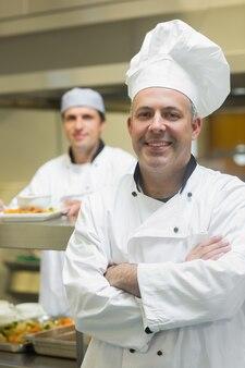 Feliz chefe de cozinha madura posando com os braços cruzados