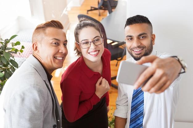 Feliz colegas bem-sucedidos do escritório que levam selfie