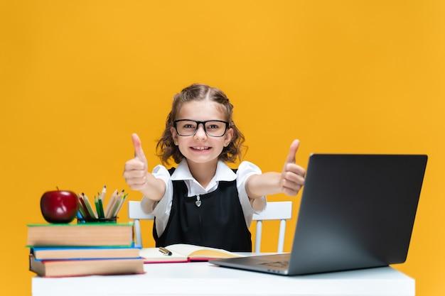 Feliz colegial caucasiana no laptop gesticulando com os polegares para cima, sentada na mesa, conceito de educação à distância
