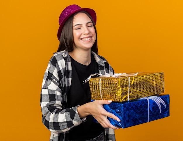 Feliz com os olhos fechados, uma jovem linda com um chapéu de festa segurando caixas de presente isoladas na parede laranja