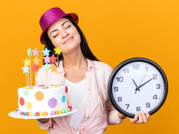 Feliz com os olhos fechados, uma jovem linda com um chapéu de festa segurando um bolo e um relógio de parede