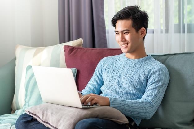 Feliz com um dia de lazer de um jovem asiático assistindo seu laptop, sentado no sofá em casa.
