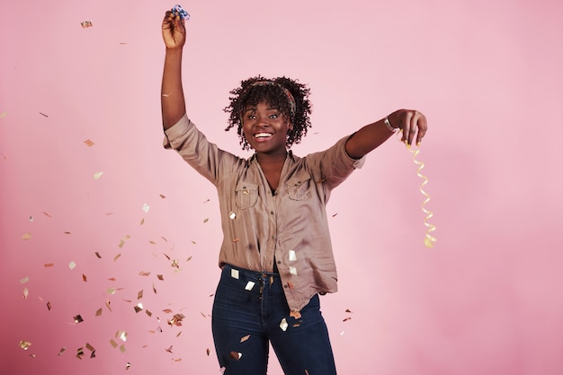 Feliz como uma criança. jogando o confete no ar. mulher afro-americana com fundo rosa atrás